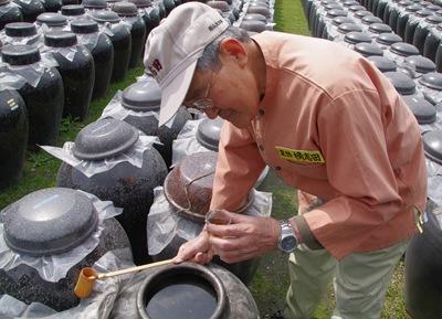 黒酢杜氏によって、かめ壺から汲み上げた黒酢を試飲